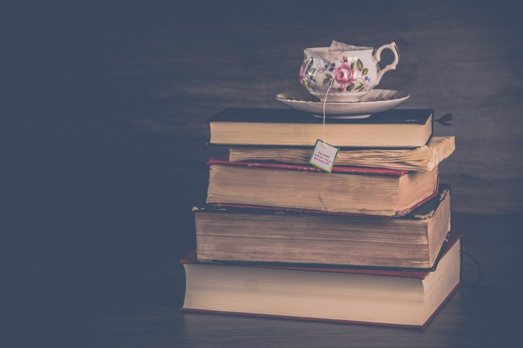 pile of books with a tea cup